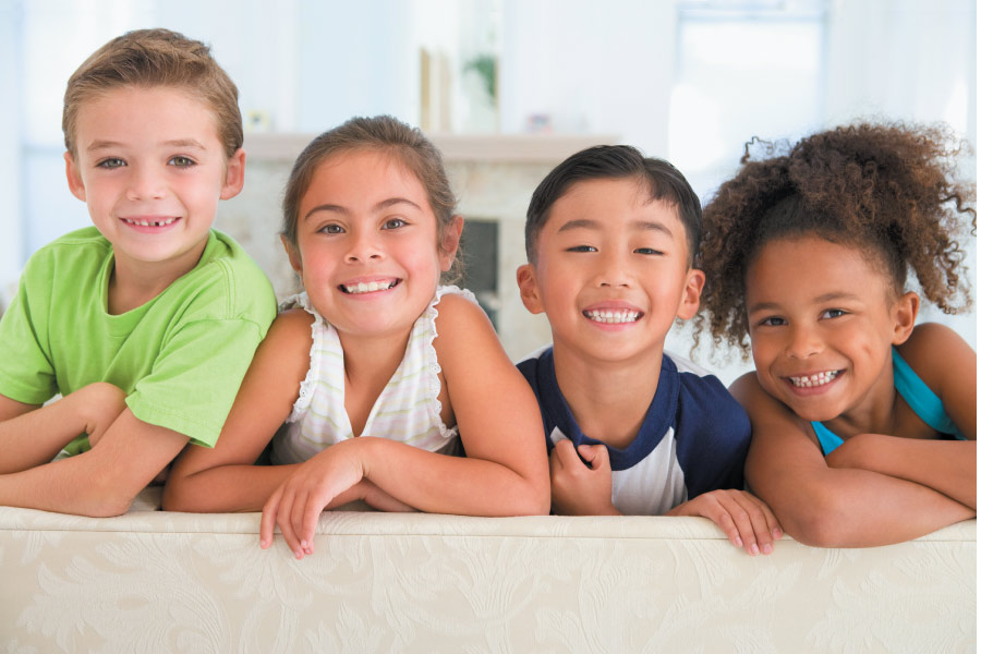 Group of children smile while on the back of a couch in Princeton, TX
